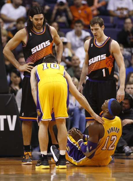 Los Angeles Lakers' Dwight Howard (12) sits on the court after he reinjured his right shoulder as teammate Steve Nash (10) and Phoenix Suns' Goran Dragic (1), of Slovenia, and Luis Scola, of Argentina, look on during the second half of an NBA basketball game, Wednesday, Jan. 30, 2013, in Phoenix. Howard left the game and did not return. The Suns won 92-86. Foto: AP in English