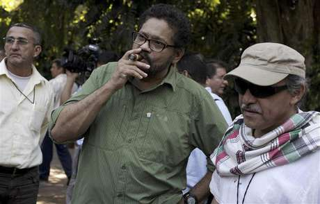 """Revolutionary Armed Forces of Colombia's (FARC) lead negotiator Ivan Marquez smokes a Cohiba cigar next to FARC negotiator Jesus Santrich (R) after a conference in Havana February 10, 2013. Colombia and the Marxist FARC rebels said on Sunday their talks aimed at ending half a century of conflict are picking up pace and making progress towards an agreement on land reform, a key point in the peace process. Speaking as they ended their latest round of negotiations in the Cuban capital, they signalled that public acrimony they had displayed in recent weeks did not represent what was happening behind closed doors. Rodrigo Granda, a senior leader of the FARC, said the discussions were moving ahead on the """"right track"""" and """"at the speed of a bullet train."""" Foto: Enrique De La Osa (CUBA - Tags: POLITICS CIVIL UNREST) / Reuters"""