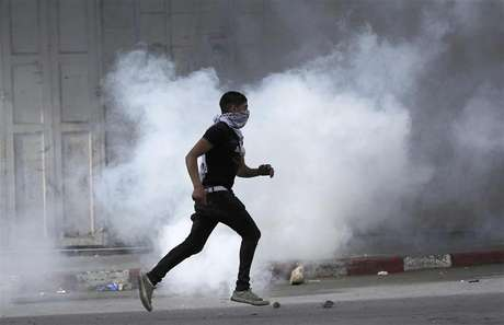 A Palestinian protester uses a sling shot to throw a stone at Israeli soldiers and border policemen during clashes at Hawara checkpoint near the West Bank city of Nablus February 24, 2013. Foto: Abed Omar Qusini / Reuters