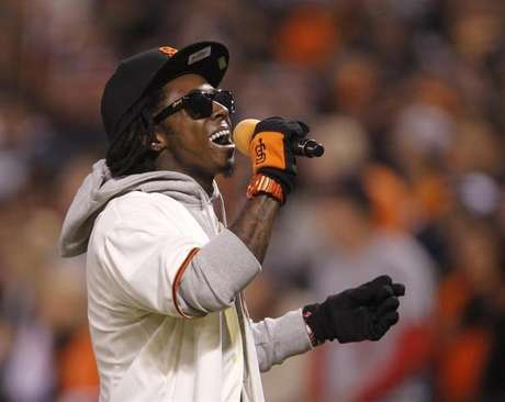 """Rapper Lil Wayne sings """"Take Me Out To The Ball Game"""" during the seventh inning stretch in Game 6 of the MLB NLCS playoff baseball series between the St. Louis Cardinals and the San Francisco Giants in San Francisco, October 21, 2012. Foto: Robert Galbraith / Reuters"""