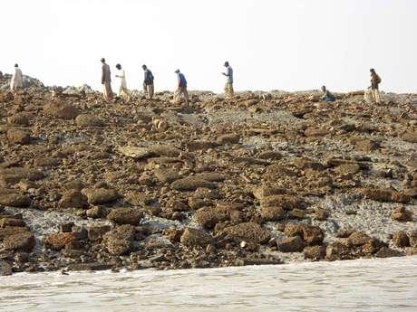 Un grupo de personas camina sobre la isla que apareció tras terremoto en Pakistán. Foto: STRINGER/PAKISTAN / REUTERS