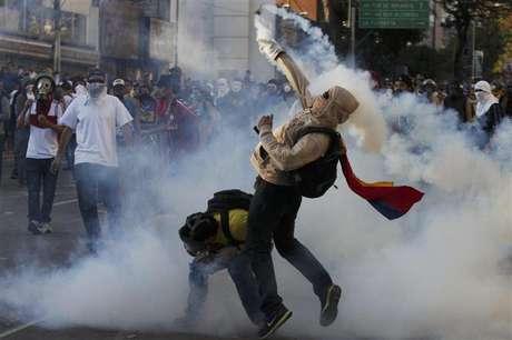 Un opositor al gobierno arroja una lata con gas lacrimógeno de la Guardia Nacional en Caracas, mar 2 2014. Criticado hasta por estrellas de Hollywood sobre la manera de lidiar con la ola de protestas antigubernamentales, el Gobierno de Venezuela se defendió el lunes ante la ONU acusando a los manifestantes de querer derrocar al presidente socialista Nicolás Maduro. Foto: Marco Bello / Reuters