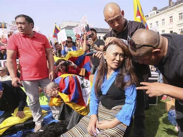 Una manifestante se rapa la cabeza durante una protesta pro derechos humanos en China, en el marco de la visita presidente chino, Xi Jinping, en Bruselas, Bélgica. Foto: EFE en español
